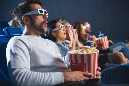 Photo pour Choqué amis multiethniques dans lunettes 3d avec pop-corn en regardant le film ensemble dans la salle de cinéma - image libre de droit