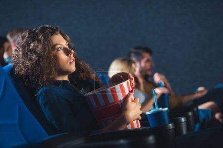 Photo pour Vue de côté de peur femme avec pop-corn regarder film dans le cinéma - image libre de droit