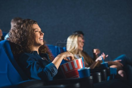 side view of cheerful woman with popcorn watching movie in cinema