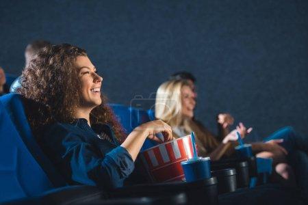 Photo pour Vue latérale d'une femme joyeuse avec pop-corn regarder film dans le cinéma - image libre de droit