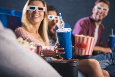 partial view of cheerful friends watching movie together in cinema