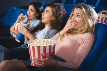 scared multiracial women with popcorn watching film together in movie theater