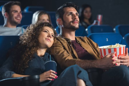 young couple with popcorn holding hands while watching movie together in cinema