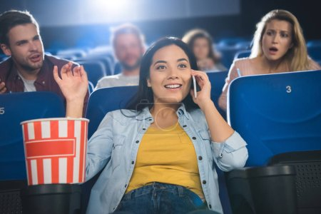 asian woman talking on smartphone while watching movie in cinema