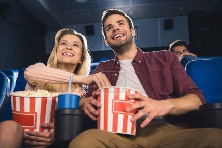 Photo pour Un couple heureux avec le maïs soufflé et soude boire regarder film ensemble au cinéma - image libre de droit