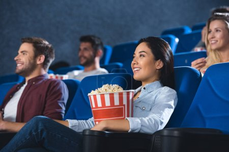 smiling asian woman with popcorn watching movie in cinema alone