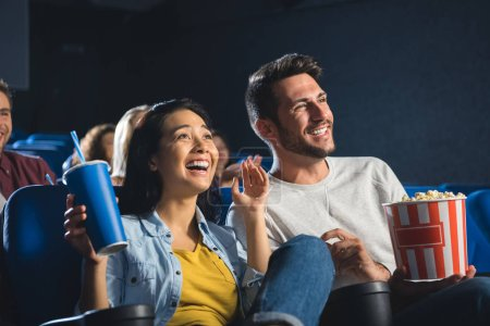 happy interracial couple with popcorn and soda drink watching film together in cinema