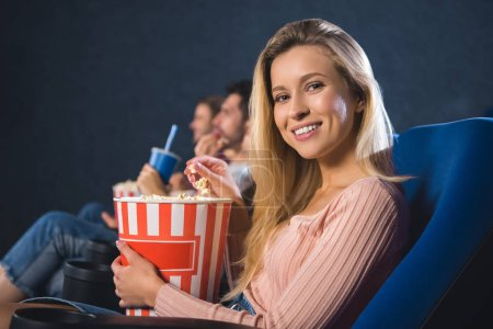 selective focus of smiling woman with popcorn in cinema