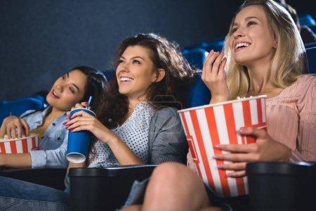 Photo pour Femmes multiraciales gaies avec pop-corn en regardant le film ensemble dans la salle de cinéma - image libre de droit