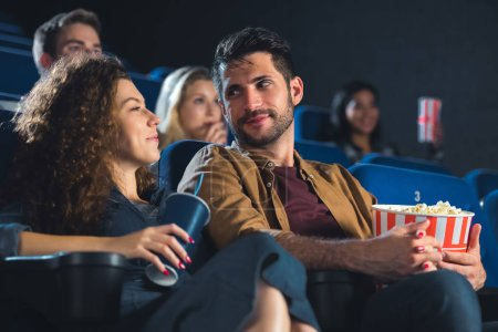 couple with popcorn holdnig hands while watching movie together in cinema