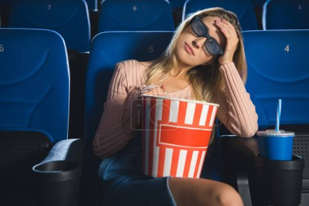 portrait of young woman in 3d glasses with popcorn watching film alone in cinema