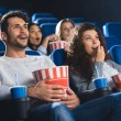 Emotional couple with popcorn watching movie toget...