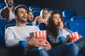 emotional couple with popcorn watching movie together in cinema