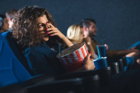 scared woman with popcorn covering eyes while watching movie in cinema