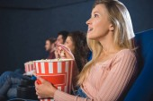 emotional multiethnic friends with popcorn watching film together in movie theater