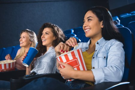 smiling multiracial women with popcorn watching film together in movie theater
