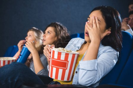 focused and scared multiracial women with popcorn watching film together in movie theater