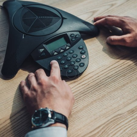 Photo pour Plan recadré d'homme d'affaires avec montre-bracelet élégant en utilisant haut-parleur sur le lieu de travail - image libre de droit
