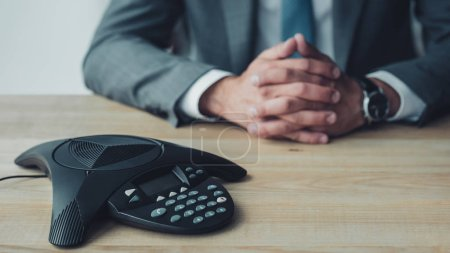 cropped shot of businessman sitting behind conference phone on table at office