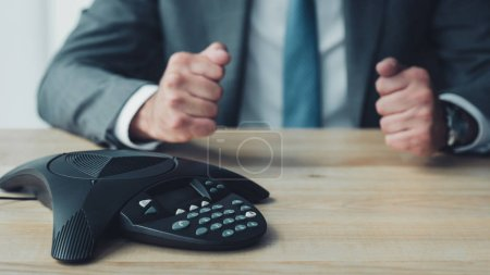 cropped shot of businessman sitting in front of conference phone and making fists at office