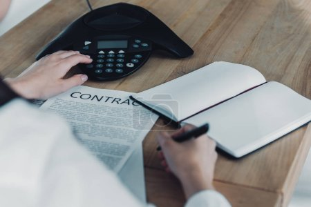 cropped shot of businesswoman with contract pushing button of conference phone on table at office