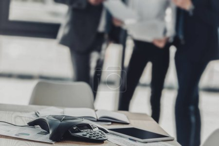 close-up shot of speakerphone with blurred business people on background at modern office