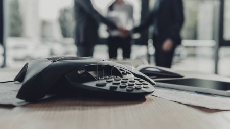 close-up shot of conference phone with blurred business people shaking hands on background at modern office