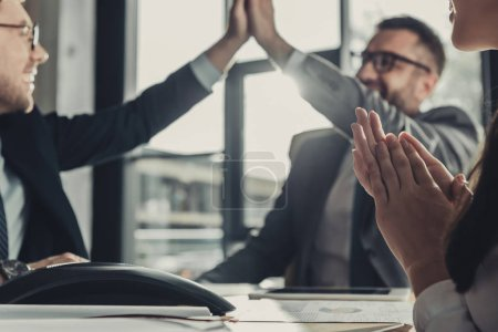 successful business people giving high five during meeting at modern office