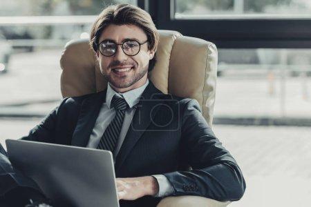 Photo pour Beau homme d'affaires souriant assis en utilisant un ordinateur portable dans un fauteuil et en regardant la caméra - image libre de droit