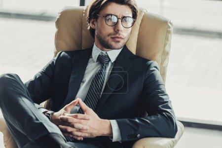 Photo pour Bel homme d'affaires pensif assis dans le fauteuil et en regardant loin de bureau moderne - image libre de droit
