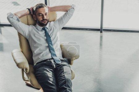 Photo pour Vue grand angle de bel homme d'affaires relaxant sur fauteuil de luxe au bureau moderne - image libre de droit