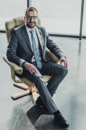 high angle view of handsome happy businessman sitting on luxury armchair and looking at camera at modern office