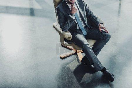 Photo pour Recadrée tir de bel homme assis sur le fauteuil de luxe au bureau moderne - image libre de droit