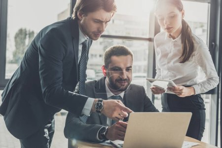 successful business people pointing at screen and using laptop together at modern office