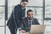 handsome successful business people working with laptop together at modern office