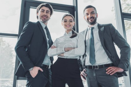 Photo for Bottom view of group of smiling young business people standing at modern office and looking at camera - Royalty Free Image