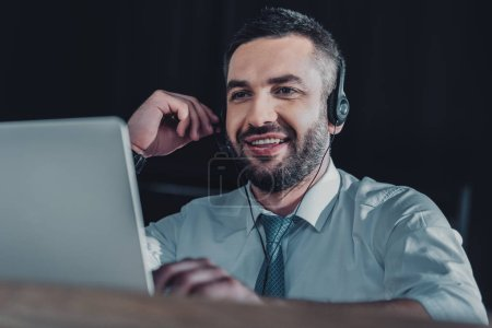 smiling support hotline worker with laptop and microphone at work