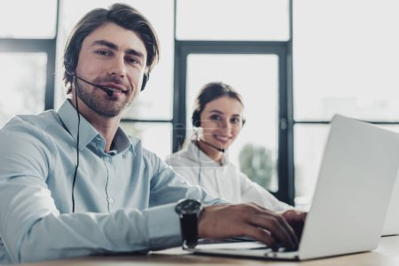 male and female call center managers working together at modern office and looking at camera