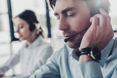 handsome call center manager in headphones with mike sitting at workplace while his colleague sitting on background
