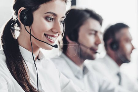 smiling young call center manageress working with colleagues