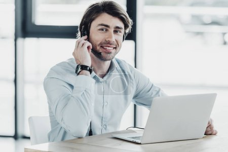 smiling call center worker with laptop looking at camera while sitting at workplace