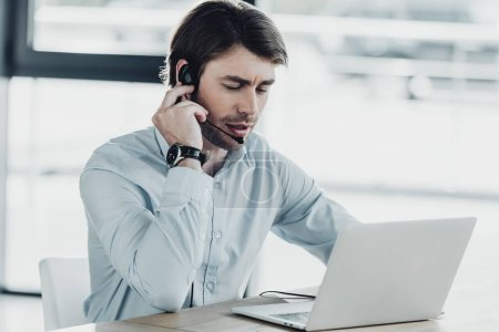 confident call center worker with laptop sitting at workplace