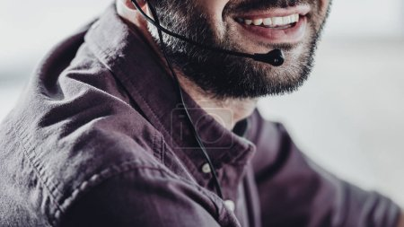 cropped shot of smiling call center worker with microphone