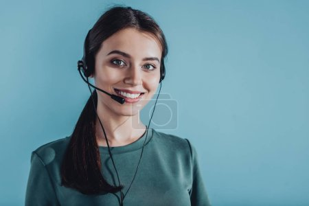 Photo for Attractive smiling female call center worker looking at camera isolated on blue - Royalty Free Image