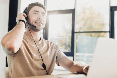 Photo pour Beau jeune travailleur de centre d'appels travaillant dans un bureau moderne - image libre de droit