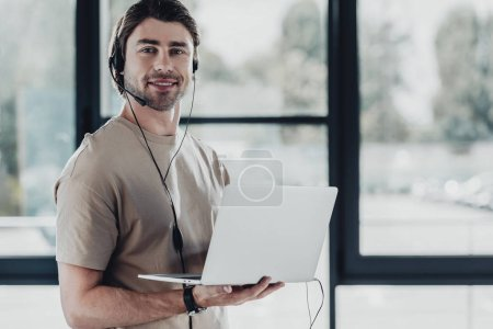 handsome young support hotline worker with laptop and headphones