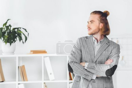 handsome businessman standing in office with crossed arms and looking away