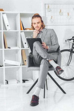 Photo for Pensive businessman looking at clipboard and sitting in chair - Royalty Free Image