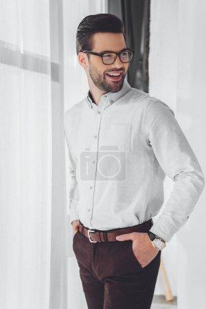Photo pour Sourire d'homme d'affaires avec les mains dans les poches à la recherche de suite - image libre de droit