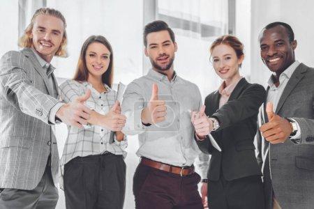 Foto de Empresarios multiculturales sonrientes mostrando los pulgares para arriba - Imagen libre de derechos